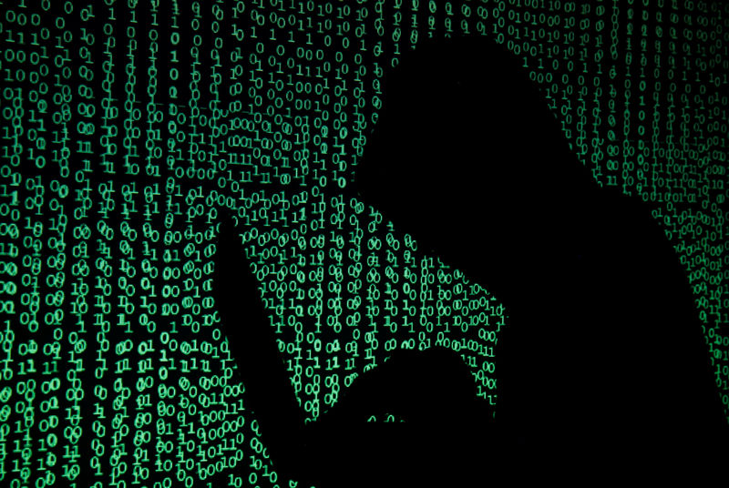© Reuters. Hooded man holds laptop computer as cyber code is projected on him in this illustration picture